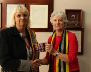 Dr Marie Nelson (right) presents a gift to Bega Valley Shire Council General Manager Leanne Barnes from the young women of Mane Hat in appreciation for Council�s support over the years. The gift is a purse made from traditionally woven tais and sewn on a treadle machine.