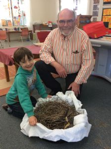 Hayden Kingston shows a nest to Bandara student, Lincoln Morris. The nest inspired the children to create their own from natural materials found in the playground.