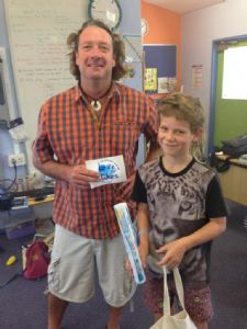 Otis Waratah of Tanja public school receives his artwork prize from Love Our Lakes project officer, Brett Weingarth.