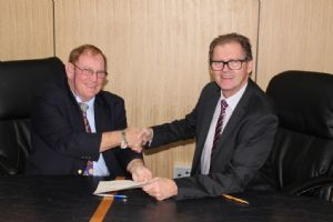 Mayor Michael Britten and Mayor Lindsay Brown shake hands after signing the MOU.